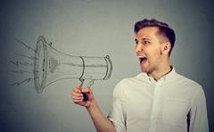Young man holding screaming in megaphone Stock Photos