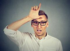 Young man in glasses showing loser sign on forehead Stock Photos