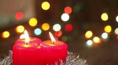 Three burning Christmas candles. Blurred background with Christmas garland Stock Footage