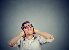 Annoyed stressed man covering ears looking up stop making noise Stock Photos