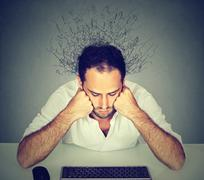 Sad man with brain melting into lines looking at computer keyboard Stock Photos