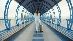 Business woman in a white suit goes on teklyannomu tunnel. Lucky bag on wheels Stock Footage
