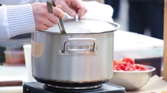 Cauldron with yellow soup cooked over a stove in the street and stirred paddle. Stock Footage