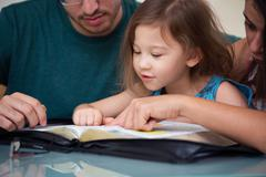Family Reading the Bible Together Stock Photos