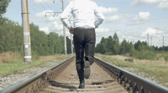 Businessman runs along the rails from camera Stock Footage