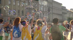 Happy teenagers group playing with soap bubbles on crowded square - sunny summer Stock Footage