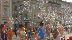 Happy children playing with many soap bubbles on square, bubbles in wind - pan Stock Footage