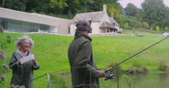 4K Happy mature couple going fishing together in the English countryside Stock Footage