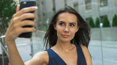 Beautiful, smiling woman take a picture of herself with a smartphone. selfie Stock Footage