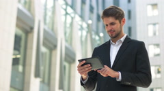 Handsome businessman read news on Tablet Computer, urban street public space Stock Footage
