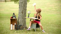 Little Child Sitting at School Desk Outside Flying an Airplane Stock Footage