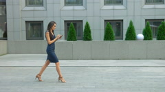 Fashionable woman using tablet pc walking outside. Modern businesswoman wearing Stock Footage