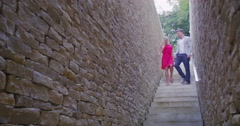 4K Attractive young couple walking down stone steps stop to share a kiss Stock Footage