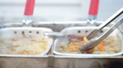 Tongs Separating Fries in Deep Fryer Stock Footage