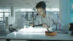 4K Scientific research engineers working in lab building electronics & robotics. Stock Footage