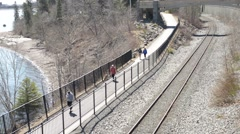 People Walking on Path Next to Water and Train Tracks Stock Footage