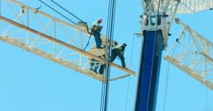 Industrial workers prepare crane assembly at construction site development 4K Stock Footage