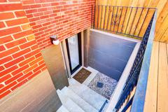 Exterior steps lead to underground basement of the brick house. Northwest, US Stock Photos