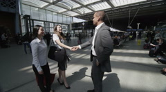 Businessman and two businesswomen meet and shake hands at St. Pancras railway Stock Footage