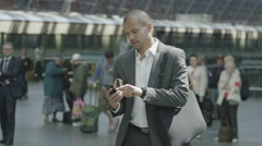 Cheerful businessman waiting for a train gets a text message which makes him Stock Footage