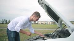 Man looking at engine of car. man repairing broken car Stock Footage