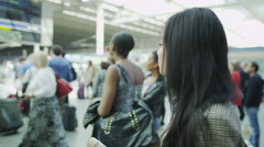 Beautiful young woman at a train station stands looking at departure boards Stock Footage