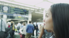 Beautiful young woman at a train station stands on her own looking at the Stock Footage
