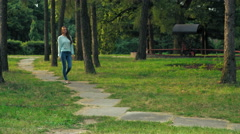 Young brunette girl is on a path in the park Stock Footage
