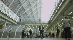 Cheerful businessman walking through St. Pancras railway station in London Stock Footage