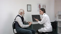 Doctor woman communicates to elder patient the good results of MRI scans Stock Footage