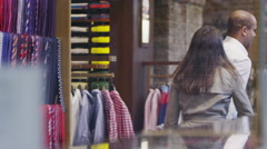 Attractive young couple shopping together in a man's clothing shop Stock Footage