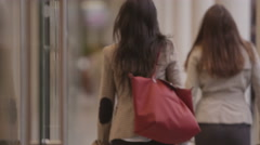 View from behind of 2 attractive female friends walking Stock Footage