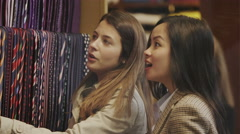 2 attractive female friends shopping together in a man's clothing store Stock Footage