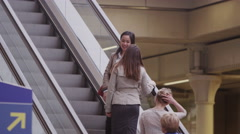 2 young female friends or business colleagues chat as they ride the escalator Stock Footage