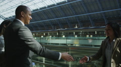 Businessman and businesswomen meet and shake hands at St. Pancras Stock Footage