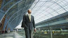 Attractive cheerful businessman walking through St. Pancras railway station in Stock Footage