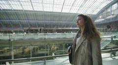 Attractive businesswoman walking through St. Pancras railway station in London Stock Footage