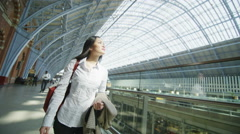 Beautiful young woman traveling on her own through St. Pancras railway station Stock Footage