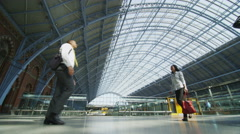 Businessman and businesswoman meet and shake hands at St. Pancras railway Stock Footage