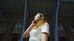 Young professional woman makes a phone call on the platform at St. Pancras Stock Footage