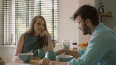 Two young parents having a conversation at the kitchen table while their Stock Footage