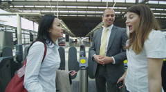 Cheerful business group chat together standing by ticket barriers in London's Stock Footage