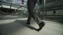 Low angle view of businessman walking through St. Pancras railway station in Stock Footage
