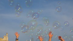 Many soap bubbles blow in the wind, hands trying to catch them in blue sky 1 Stock Footage