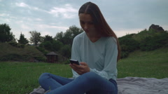A young girl sitting on blankets on the lawn in the park and gaining a message Stock Footage