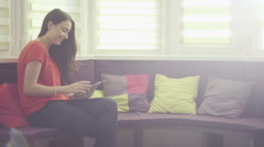 Relaxed young brunette woman sitting on sofa with tablet pc, side view Stock Footage