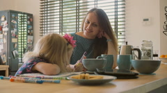 Young happy mother looks at her cute blond daughters colouring and brushes her Stock Footage