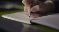 Close up of a woman hand writing in an agenda on a desk at home or office Stock Footage