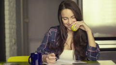 Smiling beautiful young woman sitting writing in her dining room at the table Stock Footage