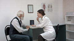 Woman doctor talking with senior patient in the office and showing him tablet Stock Footage